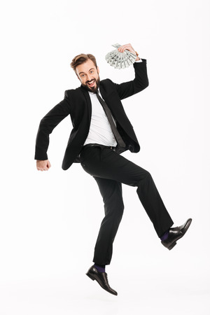 Full-length image of joyful man in business suit rejoicing his prize and holding fan of money 100 dollar bills isolated over white background Stock Photo