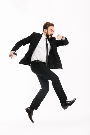 Photo of scared young businessman running isolated over white background. Looking at watch. Stockfoto