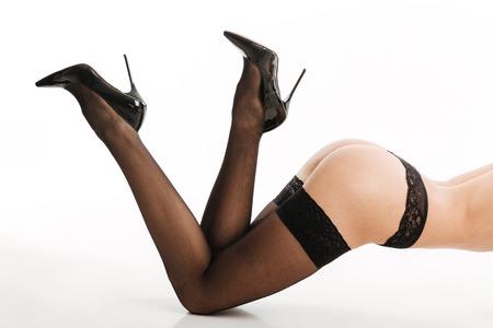 Bebouwd beeld van verbazende sexy vrouw in schoenen en elegante zwarte die damesslipjeskousen over witte achtergrond worden geïsoleerd.