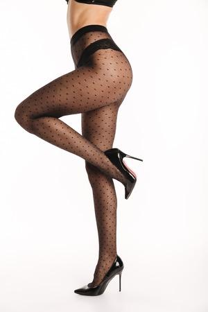 Bebouwd beeld van een sexy jonge vrouw gekleed in elegante lingerie en legging die terwijl status op hoge hielen stellen die over witte achtergrond wordt geïsoleerd