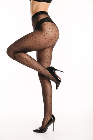 Cropped image of a sexy young woman dressed in elegant lingerie and tights posing while standing on high heels isolated over white background Archivio Fotografico