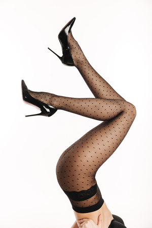 Cropped image of a seductive young woman dressed in elegant lingerie and tights posing while laying with legs raised isolated over white background