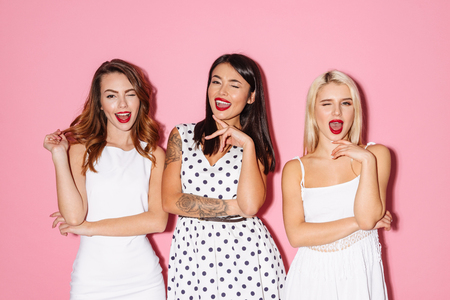 Picture of three young cute girls friends standing isolated over pink background looking camera winking. Standard-Bild