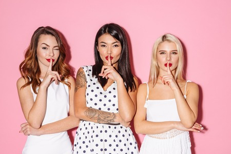Image of three pretty young ladies showing silence gesture isolated over pink background. Looking camera. Archivio Fotografico - 96986121