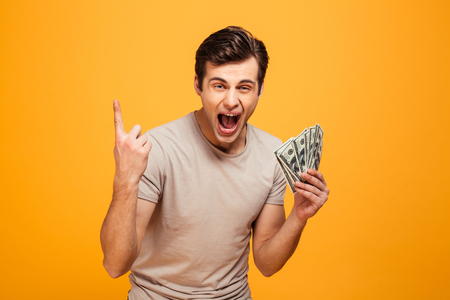 Portrait of an excited young man holding money cash and celebrating isolated over yellow background