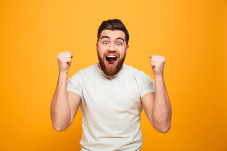 Portrait of an excited bearded man celebrating success isolated over yellow background