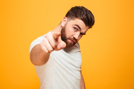 Portrait of a serious bearded man pointing finger at camera isolated over yellow background Stockfoto