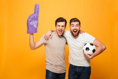 Portrait of a two happy young men holding soccer ball and foam glove isolated over yellow background Archivio Fotografico