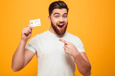 Portrait d'un homme barbu confiant, pointant le doigt sur la carte de crédit isolé sur fond jaune