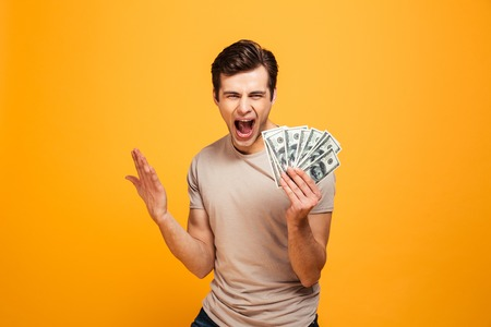 Portrait of a happy young man holding money cash and celebrating isolated over yellow background