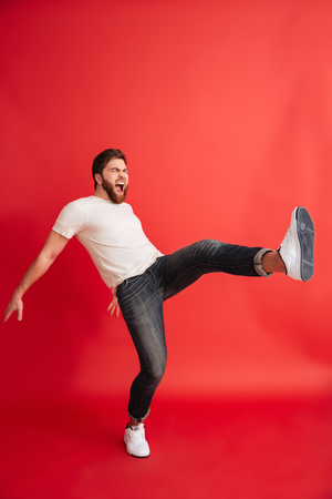 Image of emotional screaming bearded man isolated over red background wall looking aside fighting. Stockfoto