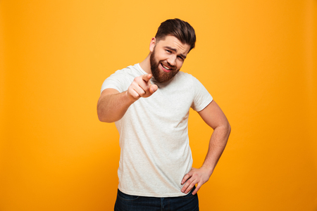 Portrait of a smiling bearded man pointing finger at camera isolated over yellow background
