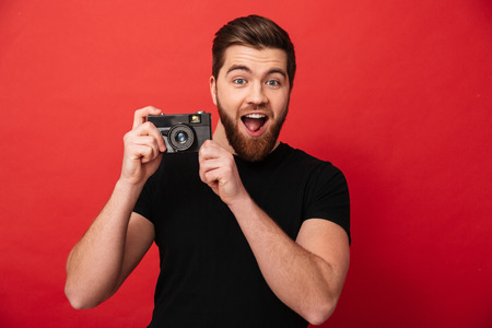 Portrait of young bearded guy 30s in black t-shirt smiling and holding retro camera in hands isolated over red background