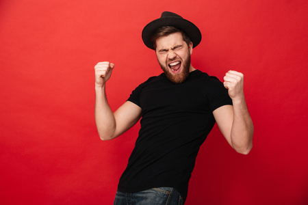 Portrait of ecstatic caucasian macho man in black outfit rejoicing and clenching fists in joy isolated over red background