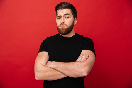 Portrait of muscular serious man 30s wearing black t-shirt posing on camera with hands crossed isolated over red background