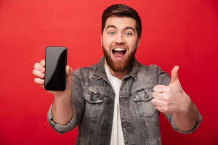 Portrait of unshaved cheerful guy demonstrating cell phone on camera and gesturing thumb up isolated over red background