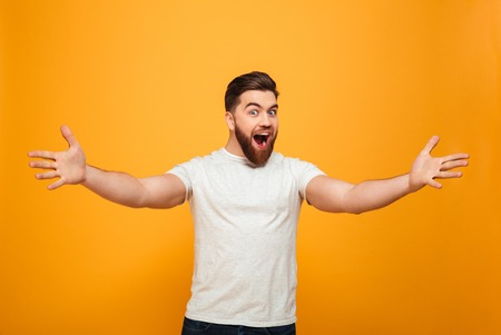 Portrait of a cheerful bearded man with outsretched hands isolated over yellow background Stok Fotoğraf