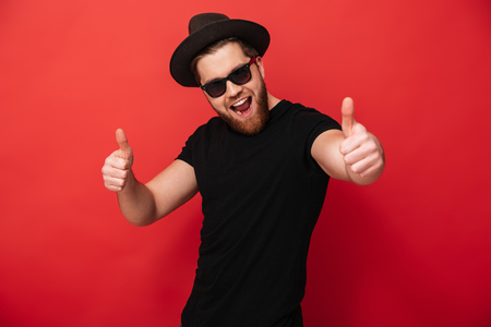 Image of excited young guy wearing black sunglasses and hat smiling and pointing fingers on camera meaning hey you isolated over red wall Stock fotó