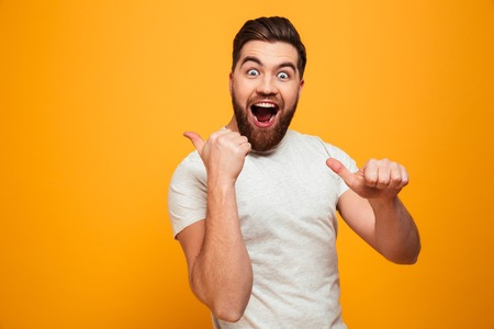 Portrait of a happy bearded man pointing fingers at copyspace isolated over yellow background Stock Photo
