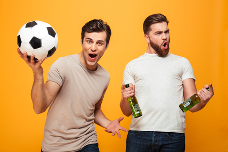 Portrait of a two cheerful young men holding beer bottles and soccer ball isolated over yellow background Stock Photo