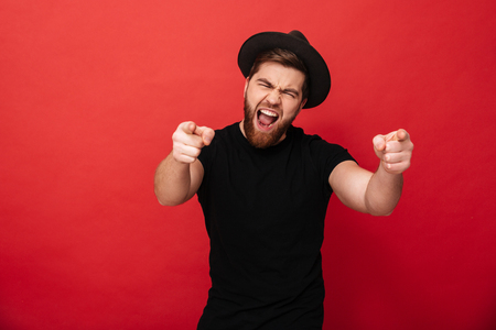 Photo of emotional fancy guy wearing black t-shirt and hat having fun and pointing fingers on camera meaning hey you isolated over red background Banco de Imagens