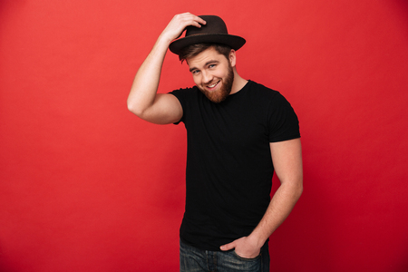 Portrait of handsome stylish man wearing black outfit touching his hat and posing with hand in pocket isolated over red background