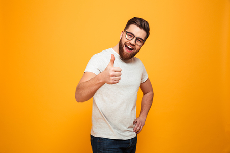 Portrait of a confident bearded man in eyeglasses showing thumbs up isolated over yellow background Stockfoto
