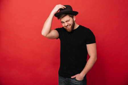 Portrait of charming caucasian man wearing black outfit touching his hat and winking while standing with hand in pocket isolated over red background