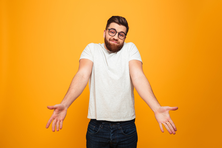 Portrait of a confused bearded man in eyeglasses shrugging shoulders isolated over yellow background Stock Photo