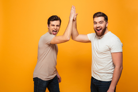 Portrait of a two delighted young men celebrating with high five gesture isolated over yellow background