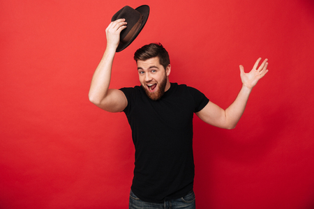 Portrait of amusing bearded man wearing black outfit posing on camera and greeting with taking off hat isolated over red background