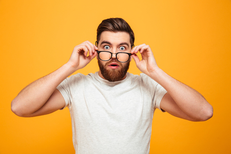 Portrait of a surprised bearded man in eyeglasses looking at camera isolated over yellow background Stok Fotoğraf