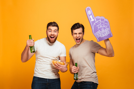 Portrait of a two cheerful young men watching football while drinking beer and eating snacks isolated over yellow background Imagens - 96987014