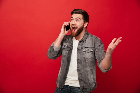 Photo of handsome excited man expressing surprise on face and gesturing while speaking on telephone isolated over red background