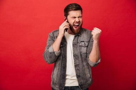 赤い背景に隔離されたモバイル会話を持っている間、顔に驚きを表現し、勝者のような拳を握りしめるハンサムな興奮した男の写真