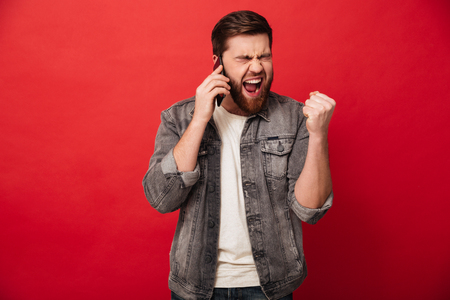 Photo of handsome excited man expressing surprise on face and clenching fist like winner while having mobile conversation isolated over red background Stockfoto