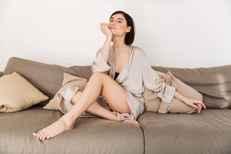 Beautiful tender woman wearing housecoat spending leisure time at home in morning and posing on camera while sitting on sofa