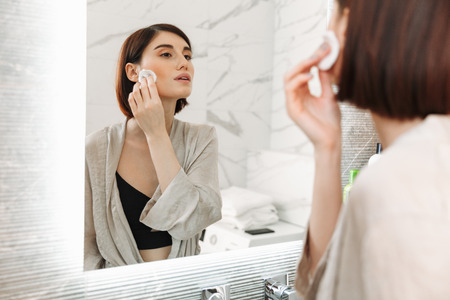 Beauty portrait of brunette woman with cosmetics on face removing makeup with cotton pad at home bathroom