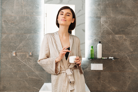 Photo of brunette beautiful woman standing near mirror and caring for skin with face cream at home in bathroom