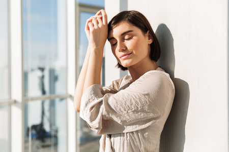Portrait of elegant woman with short dark hair in housecoat standing sunlit near window in flat and covering face in sunny morning Stock Photo