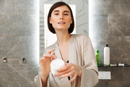Photo of brunette beautiful woman posing on camera with bank of face cream and caring for skin in bathroom