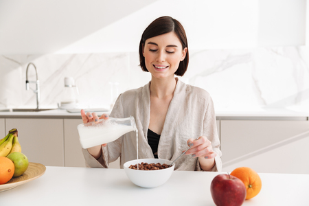 Image of brunette young woman having breakfast in kitchen in hotel room and eating cocoa balls with milk Stock Photo