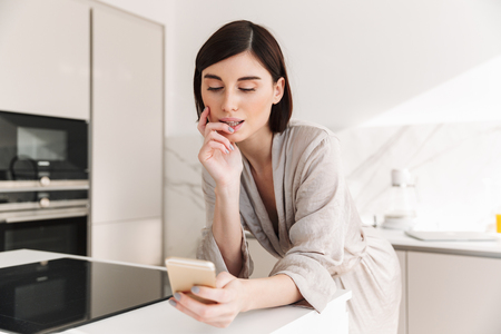 Photo of attractive woman with short dark hair wearing beautiful robe posing in kitchen and chatting or surching internet on smartphone