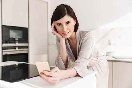 Photo of attractive woman with short dark hair wearing beautiful robe looking on camera with smile while using smartphone in kitchen