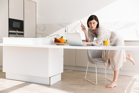 Smart concentrated woman in housecoat sitting at table in kitchen and working on laptop while having breakfast