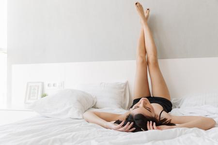 Retrato de una bella mujer acostada en la cama con las piernas en la cama en el dormitorio Foto de archivo