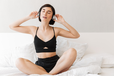 Portrait of a pretty young woman listening to music with headphones while sitting on bed at the bedroom