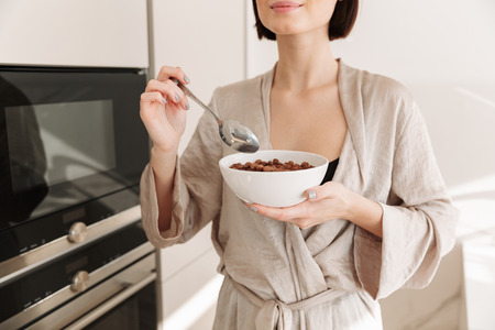 Cropped photo of healthy tender woman wearing housecoat spending leisure time at home in morning and having breakfast with cocoa balls and milk