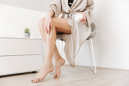 Cropped beauty portrait of slim woman with soft healthy skin applying body cream on her legs at home Stock Photo