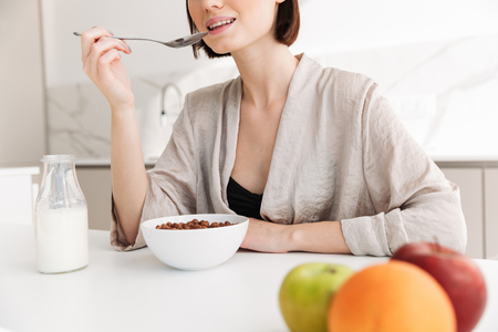 Cropped photo of satisfied woman 20s having breakfast in kitchen at home and eating cocoa balls with milk